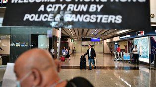 """A l'aéroport de Hong Kong, un manifestant brandit le 26 juillet une banderole proclament : """"Bienvenue à Hong Kong, ville sous la coupe de la police et des gangsters"""". (ANTHONY WALLACE / AFP)"""