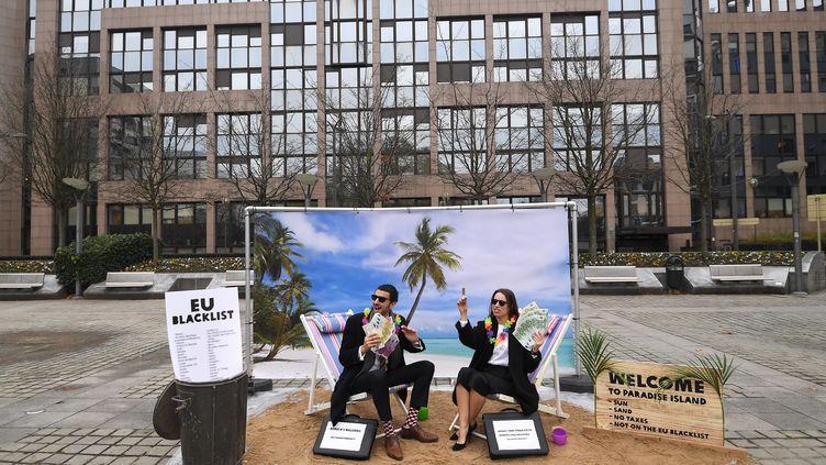 Des activistes d'Oxfam manifestent contre la liste noire des paradis fiscaux dévoilée par l'Union européenne le 5 décembre 2017 à Bruxelles, en Belgique. (EMMANUEL DUNAND / AFP)
