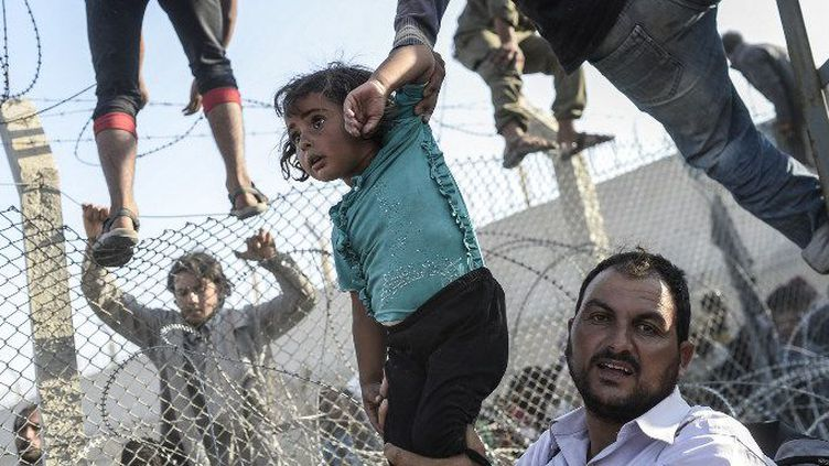 Une fillette syrienne extirpée entre grillages tordus et barbelés menaçants au point de passage d'Akçacale, entre la Syrie et la Turquie, le 14 juin 2014. La photo a reçu le Visa d'Or News au Festival international de photojournalisme «Visa pour l'image» de Perpignan, le 5 septembre 2015. (Bulent Kiliç/AFP)