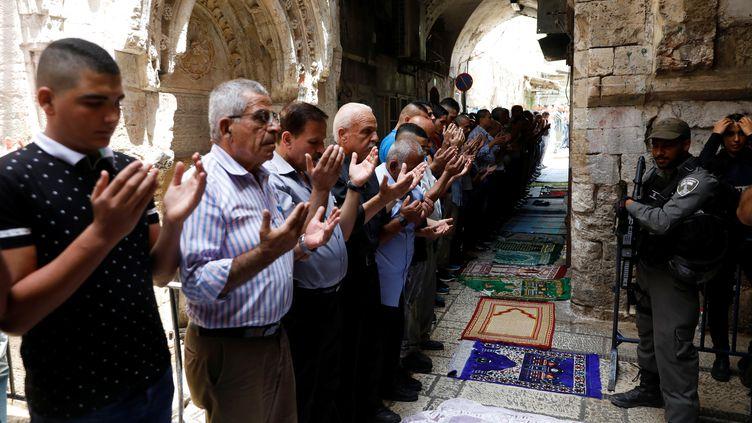 Des Palestiniens prient à l'extérieur de l'esplanade des Mosquées, le 26 juillet 2017, à Jérusalem. (RONEN ZVULUN / REUTERS)