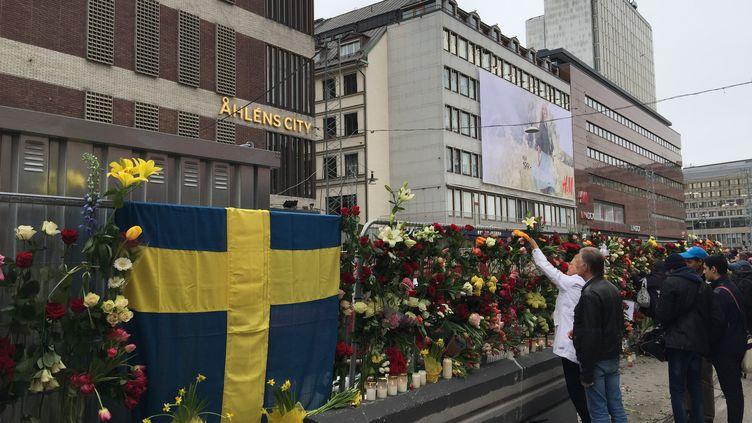 Des habitants se recueillent devant les lieux de l'attentat, à Stockholm (Suède), le 8 avril 2017. (FU YIMING / NURPHOTO / AFP)