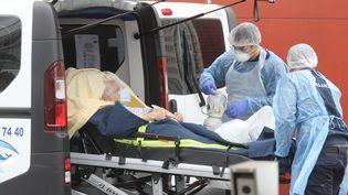 Du personnel soignant prend en charge un patient Covid-19 à l'hôpital Henri-Mondor, à Créteil (Val-de-Marne), le 3 avril 2020. (LUDOVIC MARIN / AFP)