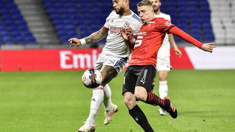 Memphis Depay et Adrien Truffert lors de la rencontre entre l'Olympique Lyonnais et Rennes pour la 28e journée de Ligue 1.  (PHILIPPE DESMAZES / AFP)