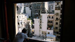 Un homme regarde les immeubles détruits à Beyrouth, au Liban, un an après l'explosion au port, le 9 juillet 2021. (ALINE LAFOY / HANS LUCAS / AFP)