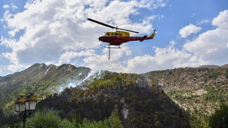 Un hélicoptère de la Sécurité civile largue de l'eau sur un incendie à Rigaud, au nord de Nice, le 3 août 2017. (YANN COATSALIOU / AFP)