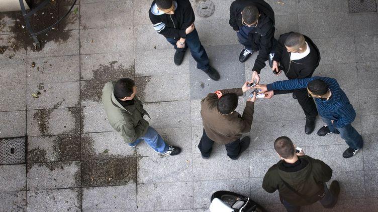 Des policiers de la brigade anticriminalité (BAC) contrôlent l'identité et les téléphones portables d'un groupe de jeunes hommes, le 9 mars 2007, à Lyon (Rhône). (JEAN-PHILIPPE KSIAZEK / AFP)