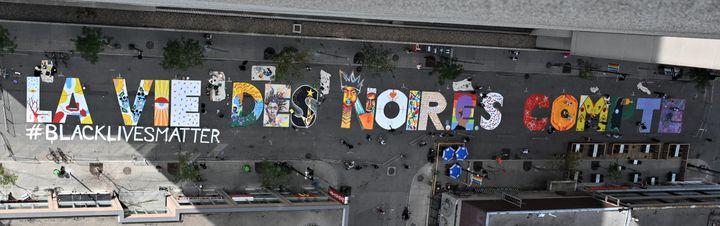 """La fresque """"La vie des noir.e.s compte"""" peinte au sol dans le quartier de Ste Catherine au centre de Montréal le 15 juillet 2020. (ERIC THOMAS / AFP)"""
