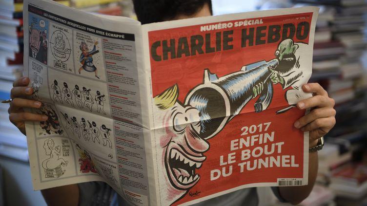 Un journaliste lit Charlie Hebdo le 3 janvier 2017, près de deux ans après l'attentat visant le journal satirique. (ERIC FEFERBERG / AFP)