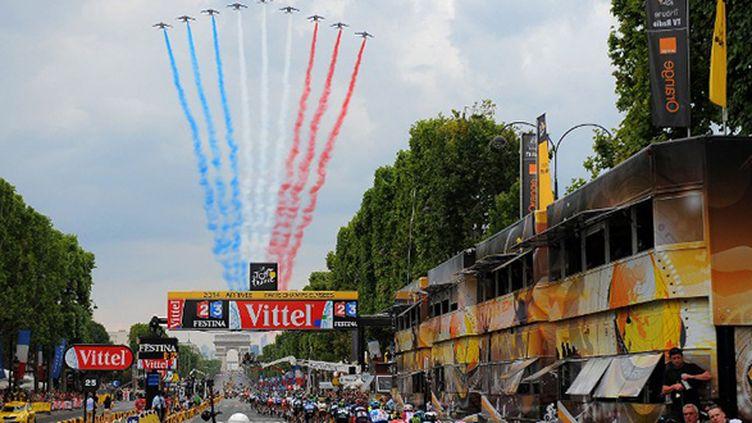 Le peloton passe sur les Champs-Elysées, salué par la patrouille de France avec l'Arc de Triomphe en ligne de mire