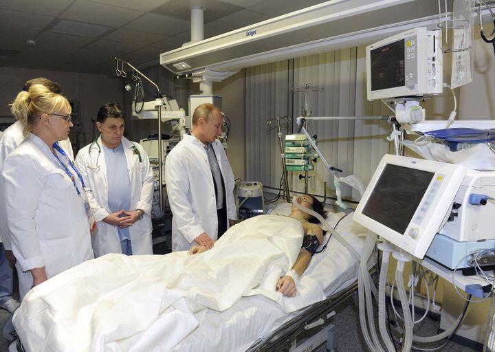 Le président russe Vladimir Poutine se rend au chevet de la skieuse russeMaria Komissarova, paralysée à vie, le 15 février 2014 à Sotchi (Russie). (RIA NOVOSTI / REUTERS)