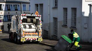Un éboueur déplace des poubelles, le 16 avril 2020 à Paris. (illustration) (JOEL SAGET / AFP)