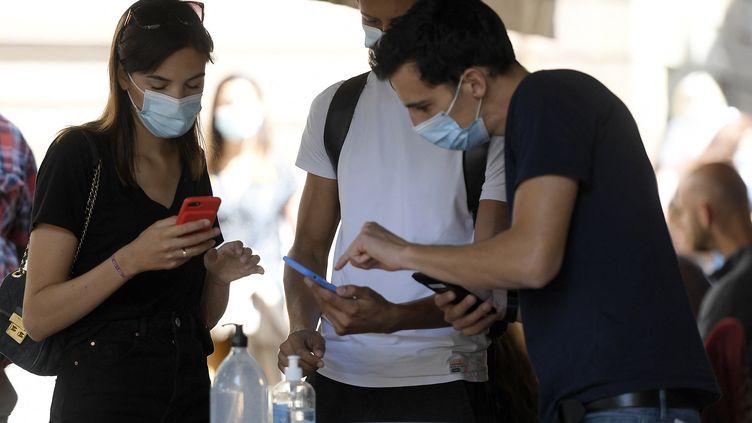 Un restaurateur contrôle les pass sanitaires de clients, le 9 août 2021. (FREDERICK FLORIN / AFP)