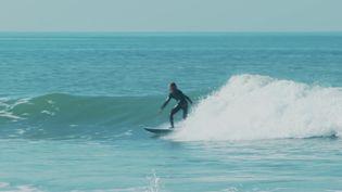 Un surfeur sur une planche en matériaux recyclés à Brétignolles-sur-Mer en Vendée. (FRANCEINFO)