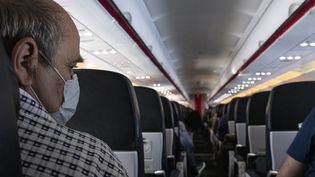 Un passager porte un masque sur un vol Air France au départ d'Athènes (Grèce), le 17 mars 2020. (ANTONI LALLICAN / HANS LUCAS / AFP)