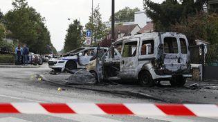 Le véhicule de police et une autre voiture, incendiés, à Viry-Châtillon (Essonne), le 8 octobre 2016. (THOMAS SAMSON / AFP)