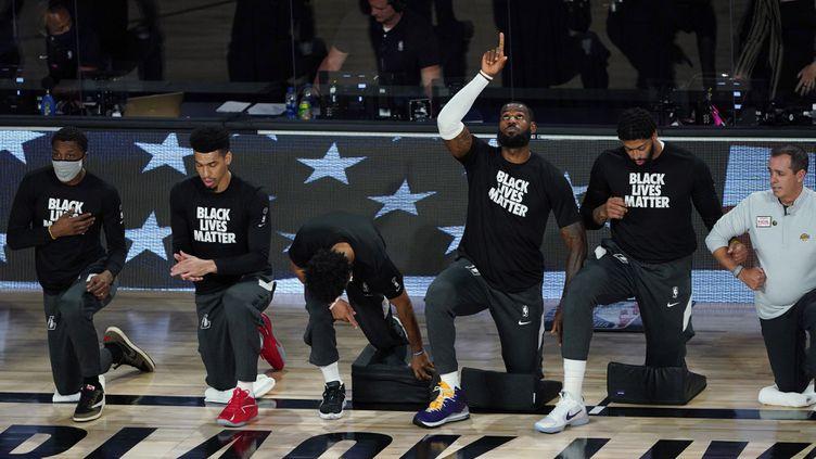 Les Los Angeles Lakers d'Anthony Davis (2e en partant de la droite) et LeBron James (3e en partant de la droite) posent le genou à terre pour le mouvement BlackLivesMatter. (POOL / GETTY IMAGES NORTH AMERICA)