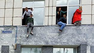 Des étudiants de l'université de Perm (Russie) sautent par les fenêtres alors qu'une fusillade est en cours, le 20 septembre 2021. (ALEXEY ROMANOV / SPUTNIK / AFP)