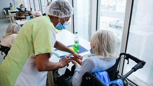 Une infirmière dans un Ehpad à Paris, le 4 mars 2021. (MARTIN BUREAU / AFP)