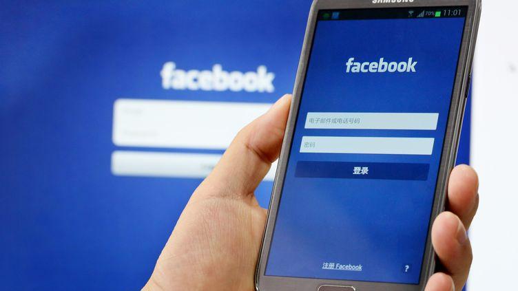 Un homme se connecte sur son application Facebook à Shanghai (Chine), le 26 septembre 2013. (ZHOU JUNXIANG / IMAGINECHINA / AFP)