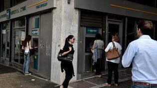 Des Grecs font la queue pour retirer de l'argent d'une banque à Athènes, le 19 juin 2015. (ARIS MESSINIS / AFP)