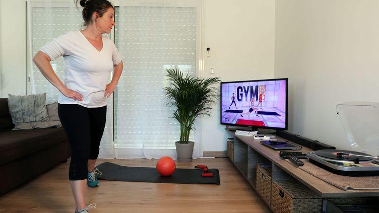 Une jeune femme confinée suit les cours de sport à la télévision. Photo d'illustration. (MAXPPP)