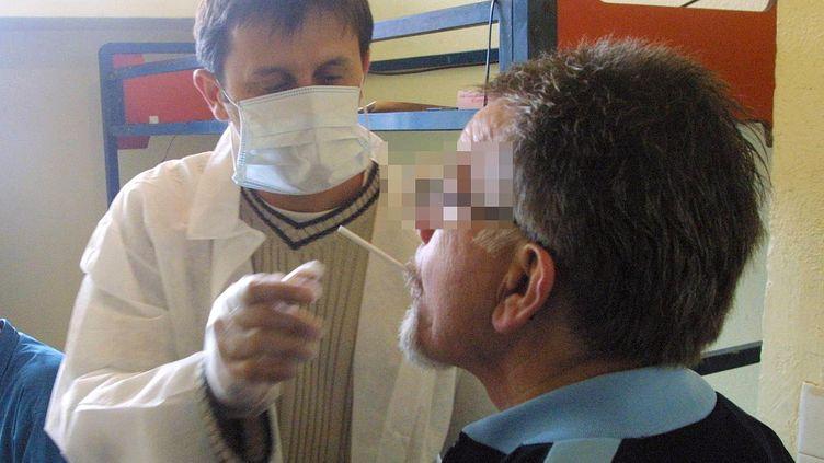 Un policier effectue un prélèvement de salive sur un détenu le 20 octobre 2003. (COR / AFP)