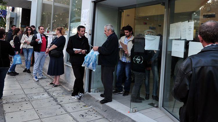Des Grecs devant une agence pour l'emploi Manpower à Athènes (Grèce), le 8 octobre 2013. (LOUISA GOULIAMAKI / AFP)