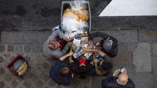 Des personnes récupérant des aliments consommables dans une poubelle devant un supermarché, à Paris. (MATTHIEU DE MARTIGNAC / MAXPPP)