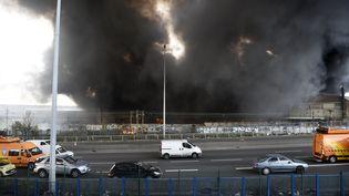 Une épaisse fumée noire se dégage d'un entrepôt en feu, le 17 avril 2015, à La Courneuve (Seine-Saint-Denis). (MARTIN BUREAU / AFP)