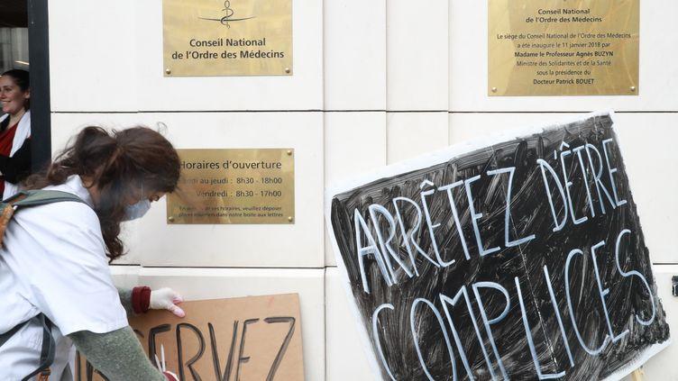 Une militante féministe dépose une pancarte devant le Conseil national de l'Ordre des médecins, lundi 18 mars. (JACQUES DEMARTHON / AFP)