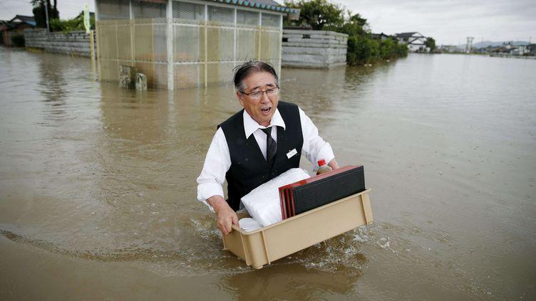 Un homme, de l'eau jusqu'à la taille, transporte des effets personnels dans une rue d'Oyama, dans la périphérie nord de Tokyo (Japon), jeudi 10 septembre 2015. (KYODO NEWS / AP / SIPA)