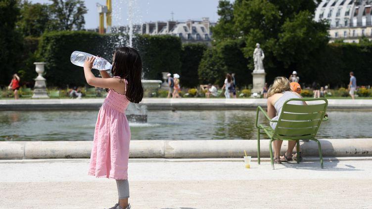 Une petite fille se désaltère, le 2 juillet 2015 à Paris. (MIGUEL MEDINA / AFP)