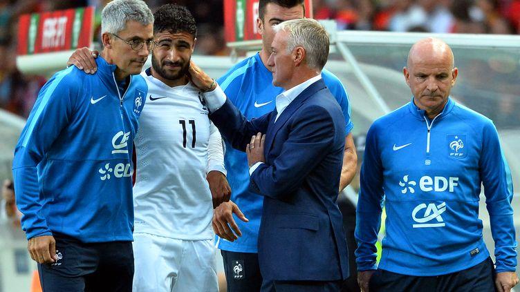 Le médecin de l'équipe de France de football, Franck Le Gall (à gauche), aide l'attaquant Nabil Fekir, blessé, lors d'un match contre le Portugal, à Lisbonne, le 4 septembre 2015. (FRANCK FIFE / AFP)