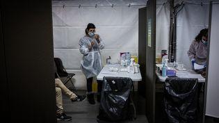 Une séance de vaccination contre le Covid-19, jeudi 14 janvier 2021, au Palais des sports de Lyon. (JEAN-PHILIPPE KSIAZEK / AFP)