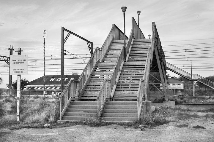 """David Goldblatt, """"Passerelle enjambant la voie ferrée, Leeu Gamka, province du Cap-Est, 30 août 2016 Passerelle enjambant la voie ferrée Le Cap-Johannesburg, avec double escalier séparé pour «blancs » et « non blancs », conformément à la loi no 49 sur les équipements publics séparés (Reservation of Separate Amenities Act) de 1953. Aujourd'hui, l'apartheid n'existe plus. Les panneaux indiquant les files séparées ont été retirés vers 1992, mais le pont demeure, au service d'une population d'environ 1 500 personnes."""" Courtesy David Goldblatt et Goodman Gallery Johannesburg et Cape Town  (David Goldblatt)"""