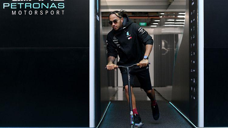 Lewis Hamilton quitte le garage de son équipe Mercedes sur une trottinette après le Grand Prix de Singapour, le 19 septembre 2019. (MOHD RASFAN / AFP)