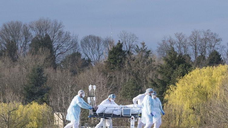 Le personnel médical transporte un patient sur un brancard vers un hélicoptère médicalisé à l'hôpital Emile-Muller de Mulhouse (Haut-Rhin),mardi le 17 mars 2020. (SEBASTIEN BOZON / AFP)