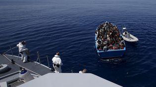 Des garde-côtes italiens viennent au secours d'un bateau transportant 300 migrants venus du continent africain, le 14 mai 2015, au large de laSicile. (ALESSANDRO BIANCHI / REUTERS)