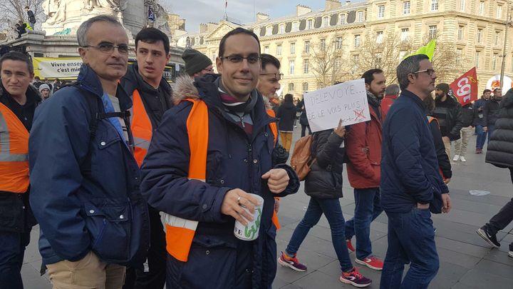 Cheminot à Niort, Lucien agite une cagnotte pour payer le bus du retour, mardi 17 décembre 2019, place de la République à Paris. (FABIEN MAGNENOU / FRANCEINFO)