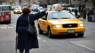 Une femme hèle un taxi, le 31 octobre 2012 à New York (Etats-Unis). (STAN HONDA / AFP)