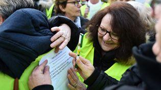 """Des manifestants """"gilets jaunes"""" signent une pétition en faveur d'un référendum populaire réclamant la destitution du président français alors qu'ils participaient à une marche civique au Mans (Sarthe), le 24 novembre 2018. (JEAN-FRANCOIS MONIER / AFP)"""