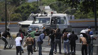 Desmanifestants de l'opposition font face aux soldats vénézuéliens, à Caracas, le 30 avril 2019. (FEDERICO PARRA / AFP)