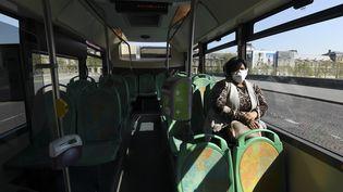 Une passagère d'un bus de la RATP s'est munie d'un masque, à Paris. (ALAIN JOCARD / AFP)