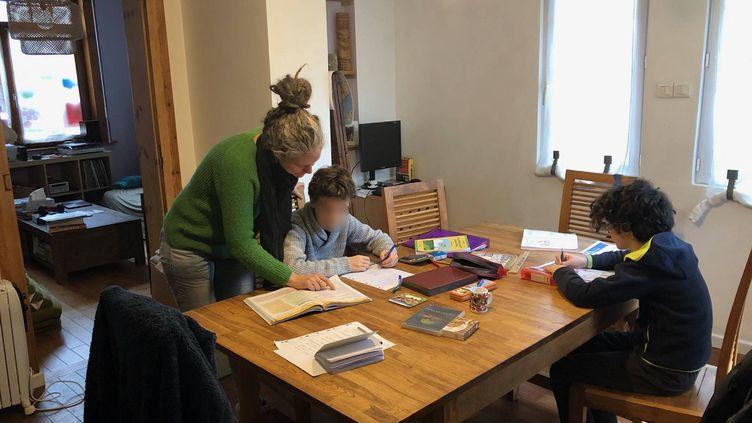 Carine et ses deux enfants, Nathanaël et Joshua, dans leur salon à Lille, en décembre 2020. (ALEXIS MOREL / RADIO FRANCE)
