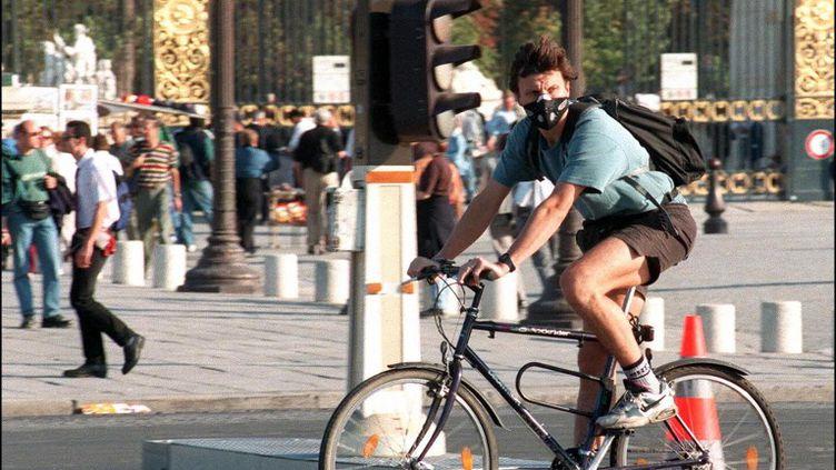 Un cycliste muni d'un masque anti-pollution, place de la Concorde, à Paris. (JOEL SAGET / AFP)