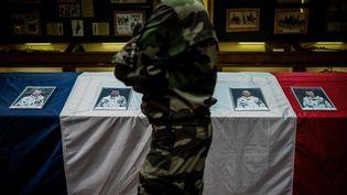 Un militaire devant le portrait des victimes, le 26 novembre 2019. (JEFF PACHOUD / AFP)