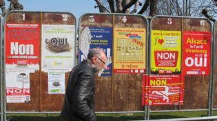 Un passant, mercredi 4 avril, devant des panneaux électoraux installés à Schiltigheim (Bas-Rhin), avant le référendum sur la collectivité territoriale unique d'Alsace. (FABIEN MAGNENOU / FRANCETV INFO)