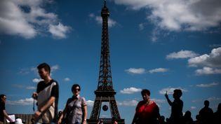 Des touristes au pied de la Tour Eiffel, le 9 juillet 2016, à Paris. (Photo d'illustration) (PHILIPPE LOPEZ / AFP)