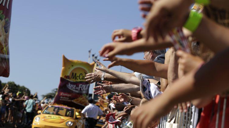 Des spectateurs tentent d'attraper des cadeaux de la caravane du Tour de France, le 20 juillet 2015, entreBourg-de-Péage (Drôme) et Gap (Hautes-Alpes). (KENZO TRIBOUILLARD / AFP)