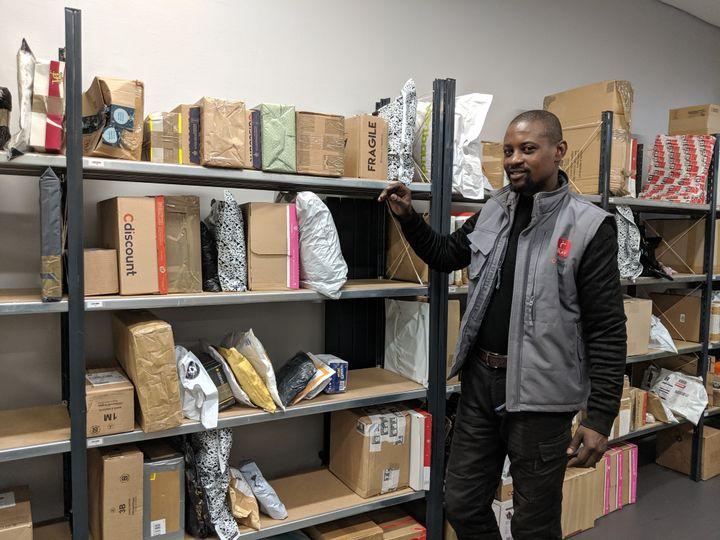"""Sylla Djibril, responsable d'un """"super relais"""" de Mondial Relay à Paris,montre les étalages dans lesquels sont rangés les colis, le 18 décembre 2019. (CHARLOTTE CAUSIT / FRANCEINFO)"""